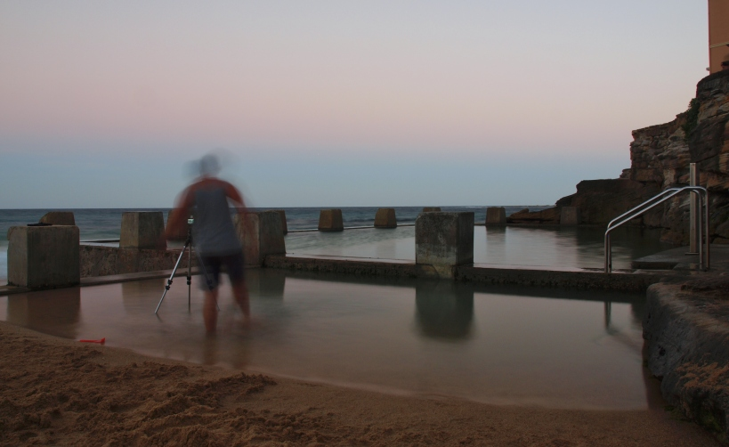Photographer kicking the water during a beautiful sunset